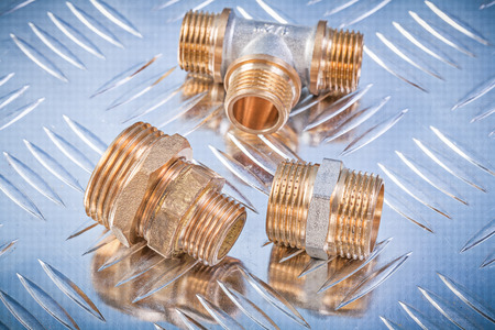 nipples: Brass hose nipples equal tee on grooved metal background plumbing concept.