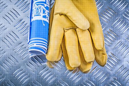 fluted: Blue blueprints leather safety gloves on fluted metal background construction concept.
