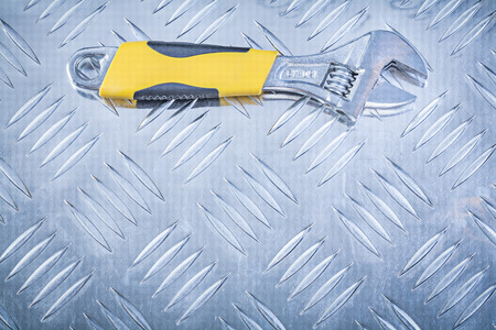 fluted: Adjustable wrench on fluted metal sheet construction concept.