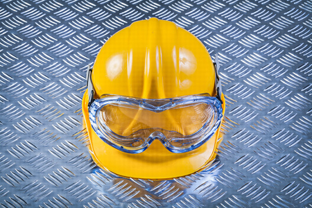 protective spectacles: Safety glasses hard hat on grooved metal plate construction concept.