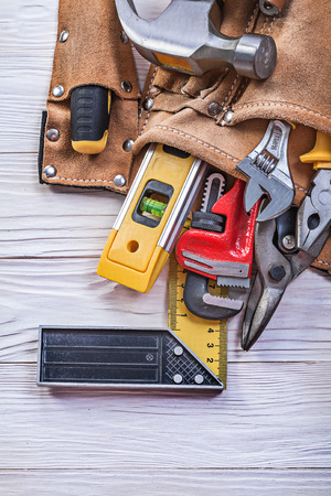 implements: Leather tool belt with building implements on wooden board construction concept. Stock Photo