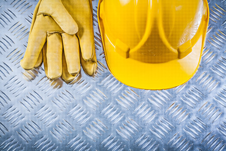grooved: Protective leather gloves hard hat on grooved metal plate construction concept.