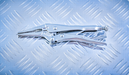 jaws: Locking pliers with jaws on grooved metal background construction concept. Stock Photo