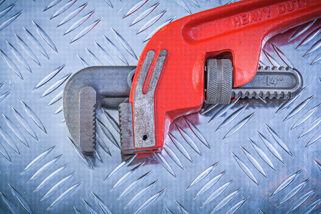 channeled: Metal adjustable monkey wrench on grooved metallic background construction concept.