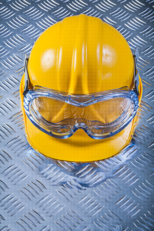 protective glasses: Protective glasses hard hat on grooved metal sheet construction concept. Stock Photo