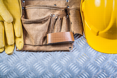 grooved: Leather building belt protective gloves hard hat on grooved metal sheet construction concept. Stock Photo