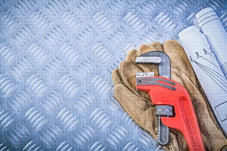 grooved: Monkey wrench blueprints leather protective gloves on grooved metal background construction concept. Stock Photo