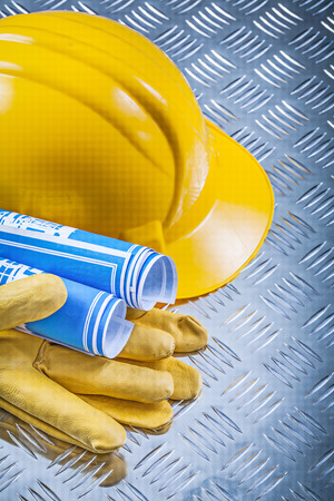 fluted: Blue blueprints hard hat safety gloves on fluted metal plate construction concept. Stock Photo