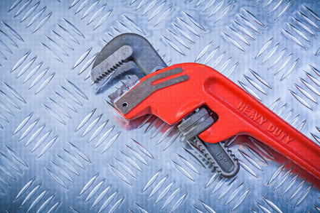 channeled: Metal pipe wrench on fluted metallic sheet construction concept.