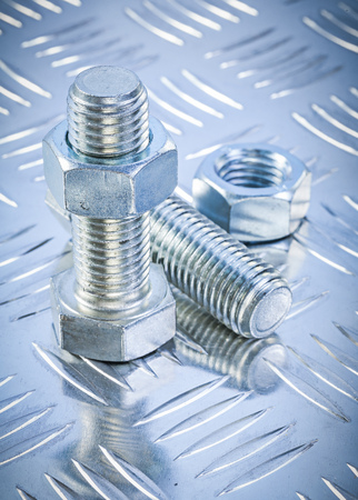 threaded: Stainless bolt details and threaded construction nuts on channeled metal background maintenance concept.