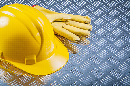 Safety leather gloves building helmet on fluted metal plate construction concept.