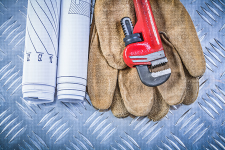fluted: Pipe wrench engineering drawings leather safety gloves on fluted metal sheet building concept.