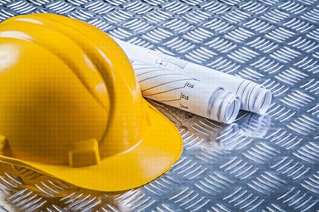 hard hat: Blueprint rolls hard hat on corrugated metal plate construction concept. Stock Photo