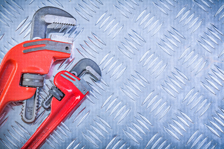 grooved: Composition of pipe wrenches on grooved metal plate construction concept. Stock Photo