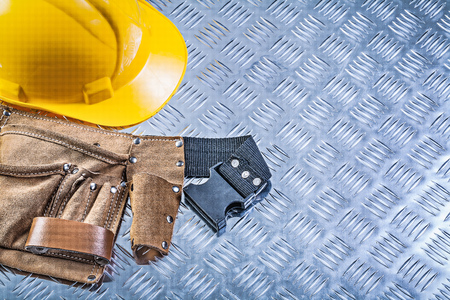 grooved: Tool belt building helmet on grooved metal plate construction concept. Stock Photo