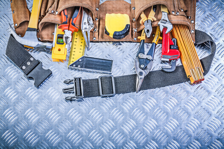 channeled: Assortment of construction tooling in leather building belt on channeled metal plate maintenance concept. Stock Photo