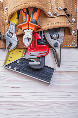 toolbelt: Leather toolbelt with construction equipment on wooden board top view. Stock Photo