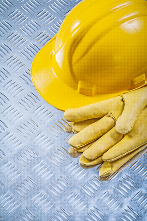 channeled: Protective leather gloves hard hat on channeled metal sheet construction concept.