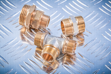 nipples: Brass hose nipples equal tee on fluted metal sheet plumbing concept.