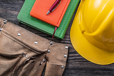 tool belt: Tool belt notepads pen safety building helmet on wooden board construction concept.