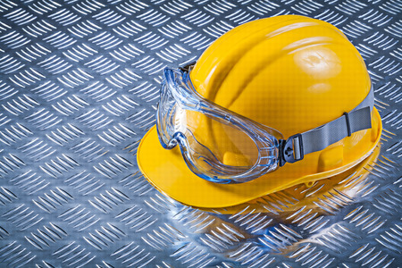 fluted: Goggles hard hat on fluted metal background construction concept.