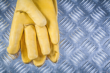 protective gloves: Leather protective gloves on fluted metal sheet construction concept.