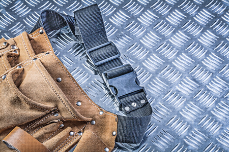 tool belt: Leather tool belt on corrugated metal plate construction concept.