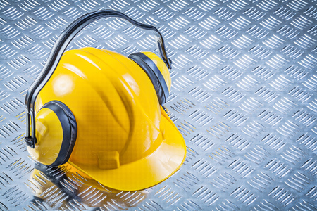 grooved: Ear muffs building helmet on grooved metal plate construction concept. Stock Photo