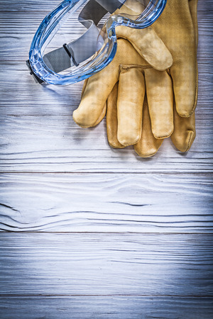 protective spectacles: Transparent goggles protective leather gloves on wooden board construction concept.