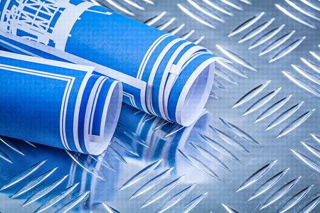 fluted: Blue rolled up engineering drawings on fluted metal background construction concept.