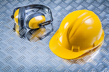 fluted: Protective ear muffs hard hat on fluted metal background construction concept. Stock Photo