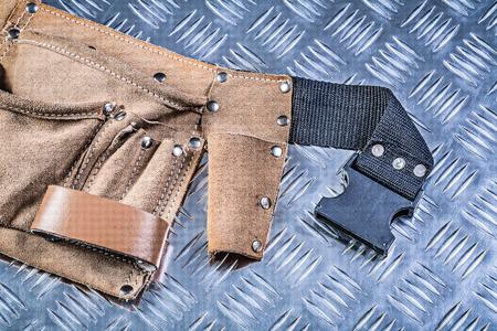 Lederen tool riem op gecanneleerde metalen achtergrond bouwconcept.