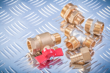 grooved: Brass nipple hose connectors equal tee check water valve on grooved metal background plumbing concept.