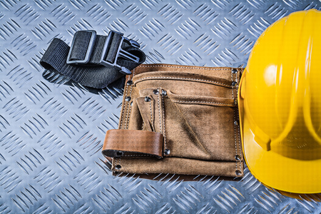 fluted: Toolbelt building helmet on fluted metal background construction concept.