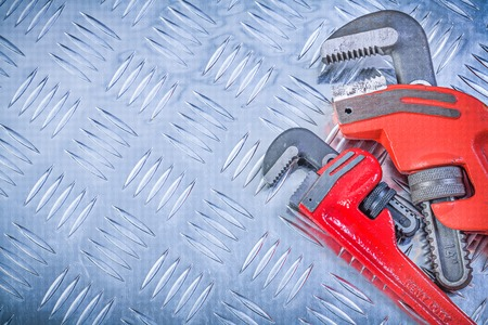grooved: Set of monkey wrenches on grooved metal plate construction concept.