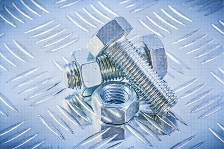 channeled: Set of bolts and construction nuts on channeled metal background directly above.