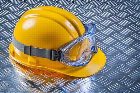 Safety goggles hard hat on fluted metal plate construction concept. Stock Photo