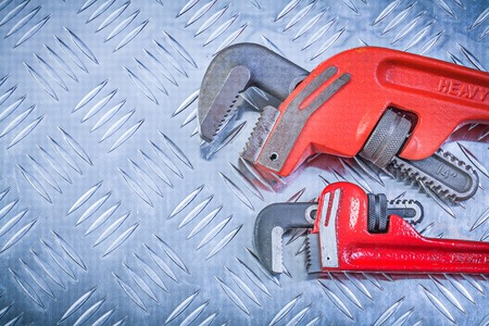 grooved: Composition of monkey wrenches on grooved metal background construction concept. Stock Photo