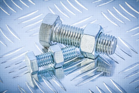 channeled: Bolts and construction nut on channeled metal background directly above.