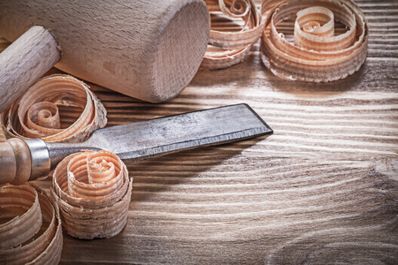 scobs: Wooden hammer firmer chisels curled shavings on vintage wood board construction concept.
