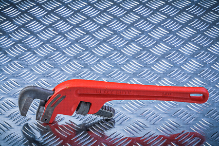 pipe wrench: Metal pipe wrench on corrugated metallic plate maintenance concept.