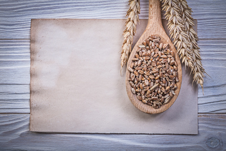 the ears of corn: Wheat rye ears corn crop wooden spoon vintage paper sheet on wood board. Stock Photo