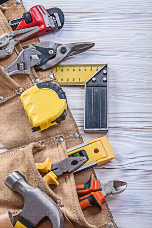 claw hammer: Construction tooling in tool belt on wooden board maintenance concept.