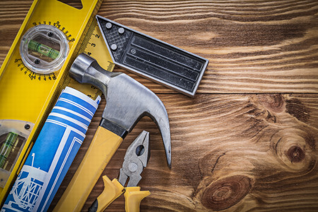 square ruler: Blue blueprints construction level square ruler claw hammer pliers on wooden board.