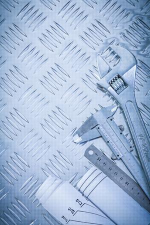 channeled: Blueprints slide caliper monkey spanner on channeled metal background maintenance concept. Stock Photo