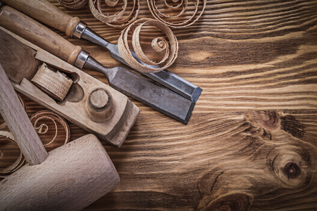 Flat chisels shaving plane curled shavings lump hammer on wooden board construction concept.