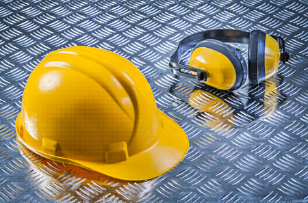 fluted: Safety earmuffs hard hat on fluted metal sheet construction concept.