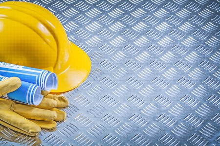 fluted: Blue engineering drawings hard hat safety gloves on fluted metal pattern construction concept.