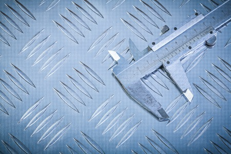 channeled: Slide caliper on channeled metal plate construction concept. Stock Photo