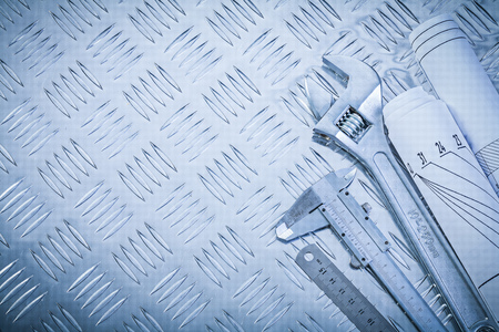 trammel: Engineering drawings vernier caliper monkey spanner on channeled metal background construction concept.